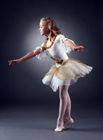 Adorable little ballerina dancing in studio