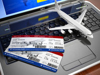 Online ticket booking. Airplane and boarding pass on laptop keyboard.