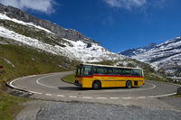 Yellow Swiss bus in a hairpin bend