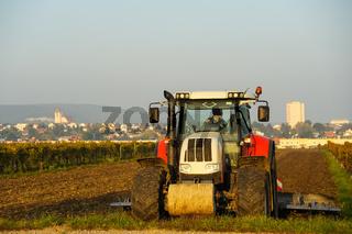 Traktor beim Eggen auf dem Feld