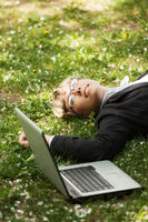 Happy business woman with laptop lying on grass