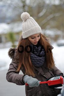 Frau fegt Schnee von ihrem Auto
