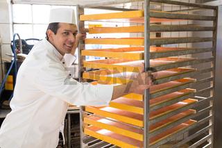 Baker with rack for bread in a bakery