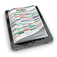 Search jobs on newspaper in tablet. Conceptual image.