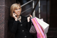 Woman with shopping bags calling on the phone