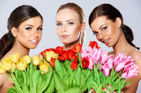 Three beautiful women with fresh spring tulips