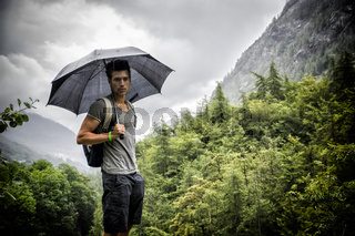 Smiling handsome young man holding an umbrella on a stormy day as he takes a walk along a trail in the mountains