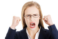 Angry and furious business woman with open mouth is screaming.