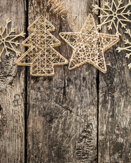Gold Christmas tree decorations on grunge wood