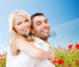 happy couple having fun over poppy flowers field