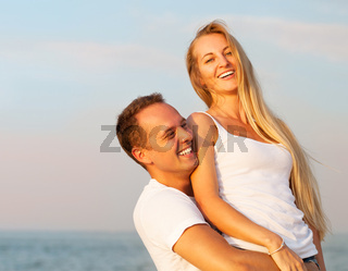 Laughing couple enjoying nature over sea background