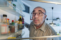 Man looking looking into the open refrigerator