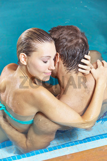 Paar umarmt sich im Schwimmbad
