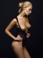 Beautiful blonde woman with naked breast in a black underwear
