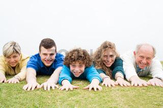 Happy family lying on green lawn