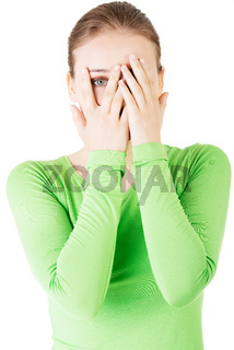 Attractive woman covering her face with both hands.