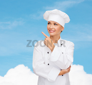 smiling female chef pointing finger to sonething
