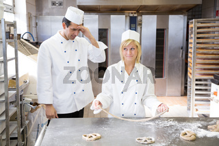Apprentice in bakery trying to form a pretzel out of dough