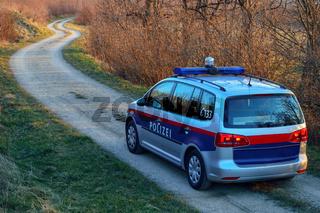 Polizeiwagen faehrt einen Weg entlang