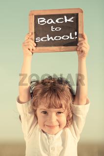Schoolchild holding small blackboard