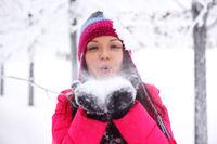 winter girl blow on snow in hands