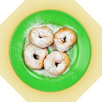 Green dish with donuts, coated with powdered sugar