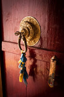 Old door at Buddhist monastery temple decorated with ancient doorknob and tassel. India, Ladakh, Spituk Gompa