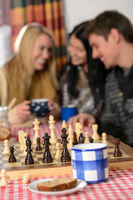 Young people play chess winter cottage countryside