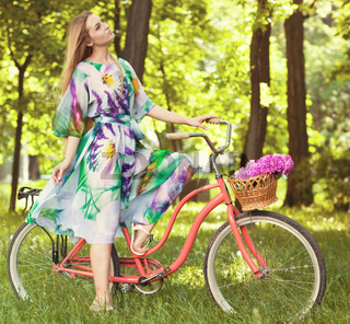Beautiful blond woman wearing a nice dress having fun in park with bicycle