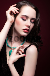 Young beautiful woman with closed eyes on red marsala background