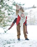 Mann trägt Frau huckepack durch Schnee