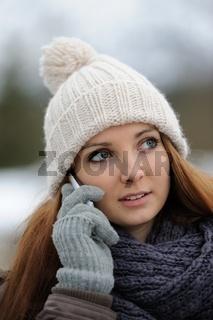 Junge Frau mit Handy in Winterkleidung