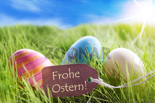 Three Colorful Easter Eggs On Sunny Green Grass With Label With German Frohe Ostern Means Happy Easter