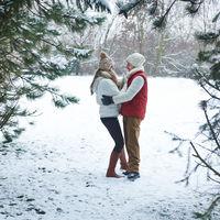 Glückliches Paar steht im Winter im Wald