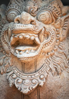Muzzle of terrible mythical monster. Stone statue from Indonesia, Bali island