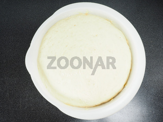 Proven dough in a white plastic bowl on black table