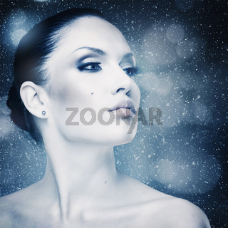 Winter freshness, abstract female portrait with falling snow as background