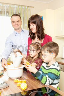 Young parents bake in the kitchen with her children