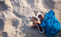 Slippers and blue textile on a sand