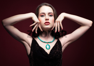 Young beautiful woman in black dress with green pistachio colour eyes on red marsala background