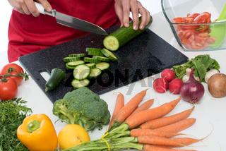 hausfrau zerschneidet eine gurke für einen salat