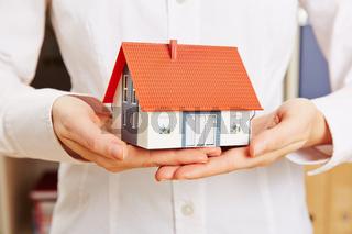 Hände halten Haus als Versicherung