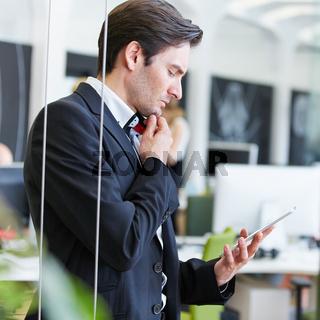 Mann im Büro schaut auf Tablet Computer