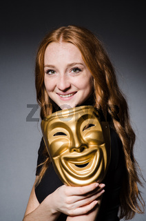 Redhead woman iwith mask in hypocrisy consept against grey background