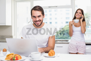 Young man using laptop at breakfast