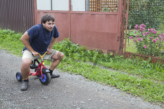 Adult man tying to ride on a small tricycle