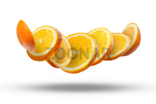 Falling slices of orange in air on white