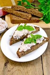 Sandwiches with cream of salmon with bread on the board