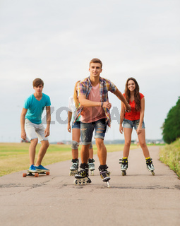 group of smiling teenagers with roller-skates