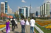 Hochzeitspaar auf einem Spaziergang in den Grünanlagen an der Al-Farabi Avenue im Bostandyksky Stadtbezirk
